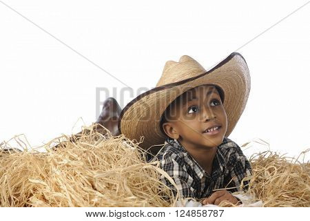 An African cowboy happily resting in the hay cowboy boots and an over-sized hat.  On a white background.