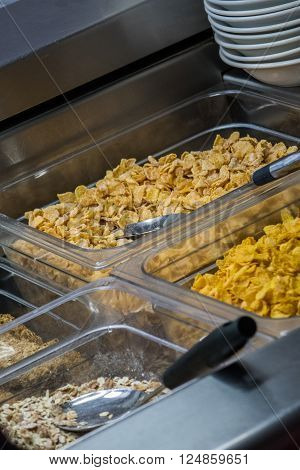 Cereal dispensers offering various kind of cereals on a self service breakfast counter in a hotel restaurant