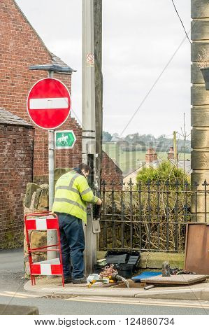 WREXHAM WALES UNITED KINGDOM - MARCH 21 2016: Openreach worker fixing BT (British Telecom) telephone line outside in the street.