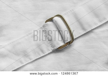 Belt with golden buckle on white linen cloth as a background
