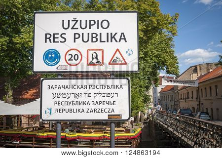 VILNIUS, LITHUANIA - JULY 15: Lithuanian road sign with text against of green tree and sky to enter Uzupis autonomous community. July 2015
