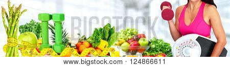 Woman with scales over fruits background.