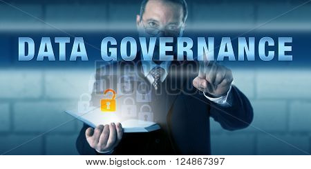 Businessman is pushing DATA GOVERNANCE on a virtual touch screen interface. Business standard metaphor and information technology concept.