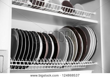 Clean dishes drying on metal dish racks on shelves