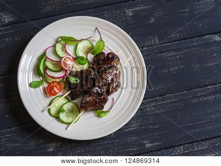 Grilled chicken liver kebabs and fresh vegetable salad on a dark wooden background