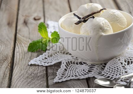 Vanilla ice cream in white bowl on rustic wooden background