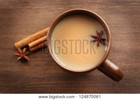 Milk tea with spices on wooden background.