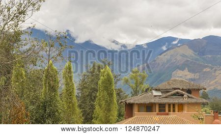 Day landscape scene photo of touristic cabins and trees with big mountain with fog at background at san pablo lake in Imbabura district, Ecuador, South America