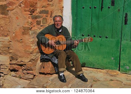CASTRILLO DE LOS POLVAZARES LEON SPAIN - MARCH 17 2013: Street singer with a guitar in Castrillo de los Polvazares Leon