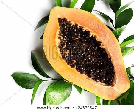 Halved papaya with leaves on white background