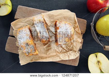 Slices of strudel with apples, walnut and raisins on parchment