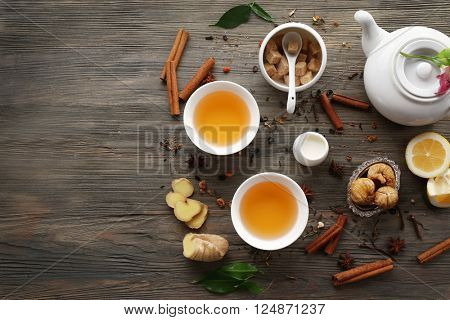 Two cups of brewed tea with ginger and spices on wooden table