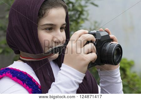 Young Little Girl Is Taking Photograph by An old Analogue Camera Strapped on Her Neck