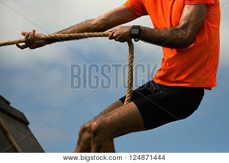 Mud race runners extreme sport.Man lying through obstacles by using ropes