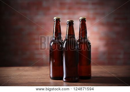 Brown glass bottles of beer on brick wall background