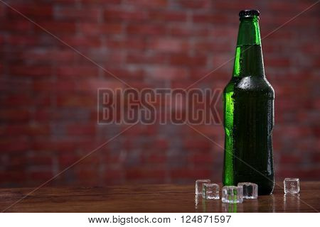Green glass bottle of beer and  and ice cubes on brick wall background
