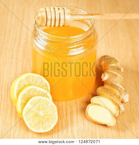 Folk remedies for colds honey, lemon, ginger root on a wooden surface