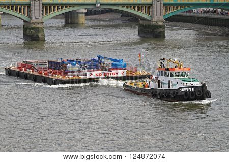 LONDON UNITED KINGDOM - APRIL 09: Tugboat and Barge at Thames in London on APRIL 09 2010. Tug Pulling Construction Platform Near Blackfriars Bridge in London United Kingdom.