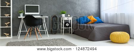 Panorama of a modern interior arranged in grey with skateboard leaning against the wall
