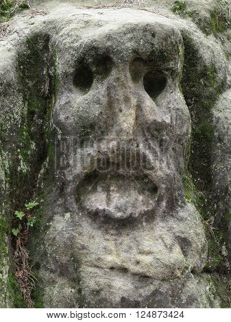 Scary Stone Heads - rock sculptures of giant heads carved into the sandstone cliff, Czech republic