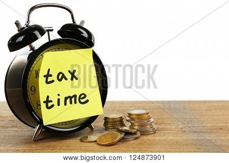 Tax time on alarm clock and coins on table