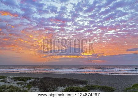 A cloudy and colorful pastel sky is reflected on the Atlantic Ocean with gently breaking waves on a Florida beach.
