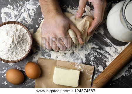 Male hands kneading raw dough on kitchen table
