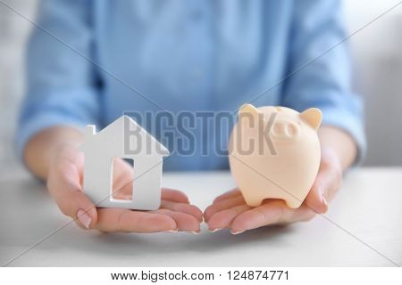 Savings concept. Woman holding piggy bank in one hand and house figure in another, close up