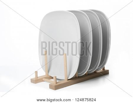 Ceramic plates in wooden stand, isolated on white