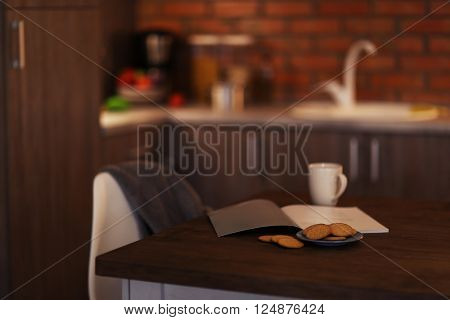 Modern table with cup and book in the kitchen