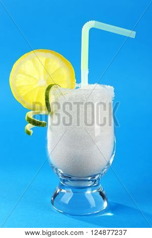Glass with granulated sugar, cocktail straw and lemon slice on blue background