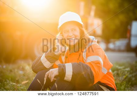 Senior woman engineer wearing protective wear in work calling phone and relaxing - outdoor at sunset