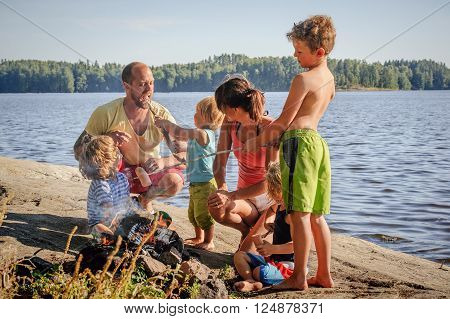 Family with four children grilling sausages over a camp fire beside a lake. The sausages are stuck onto wooden steaks gathered from the forest. Youngest son offer's father a bit from his sausage on a steak.