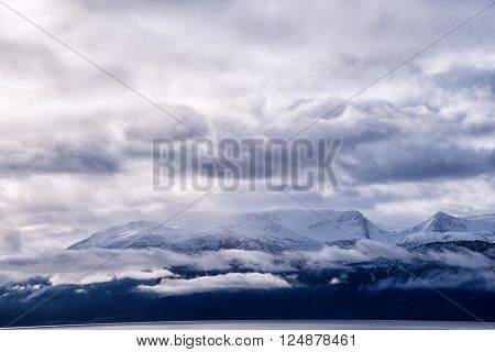 Amazing view of snow caped mountain range with storm clouds in the sky