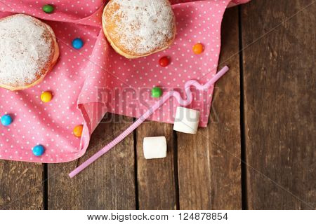 Delicious sugary donuts with pink napkin on wooden table, top view
