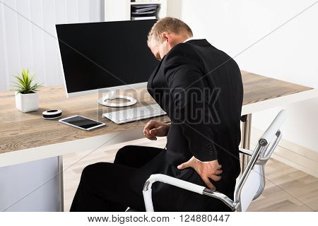 Young Businessman Suffering From Backpain While Working In Office ** Note: Shallow depth of field