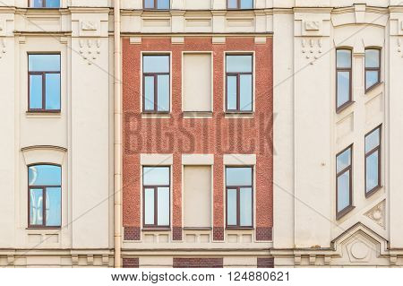 Several windows in row on facade of urban apartment building front view St. Petersburg Russia