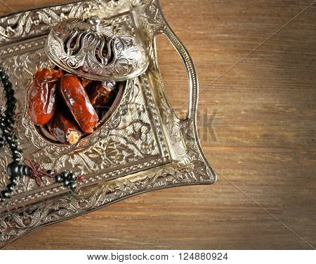 Composition of dried dates in holiday dish and rosary on wooden background