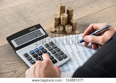 Close-up Of A Businessman Calculating Financial Report With Stack Of Coins On Desk In Office