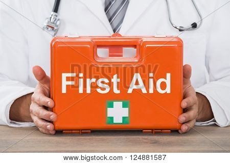 Close-up Of Young Male Doctor Hand Holding First Aid Kit Box In Clinic