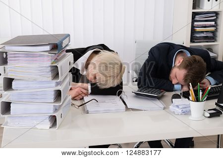Businesspeople Sleeping On Desk