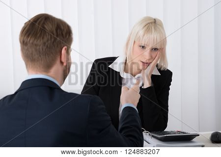 Close-up Of Boss Blaming Young Female Employee For Bad Results In Office