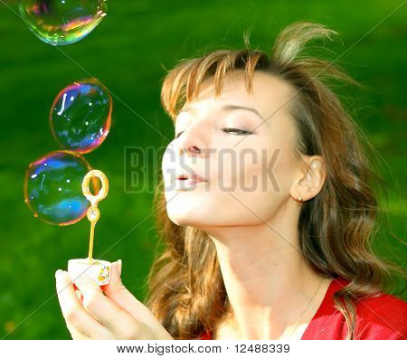 Young Girl Blowing Soap Bubbles In Spring Green Park