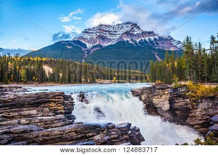 Powerful picturesque waterfall Athabasca. Pyramidal mountain covered with the snow. Canada, Jasper National Park
