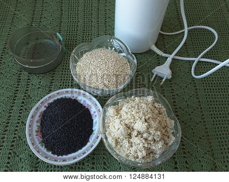 Black and white sesame seeds on a plate grind in a coffee grinder for tahini paste, cooking food for a vegetarian diet
