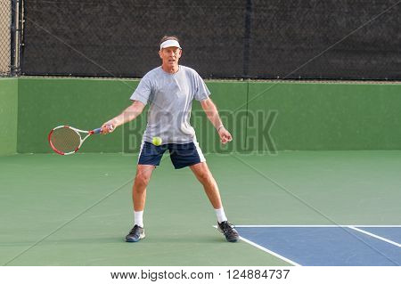 Senior age man showing perfect open forehand stance.