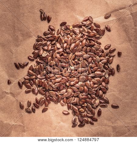 Healthy food organic nutrition. Flax seeds linseed heap on paper background. Square format
