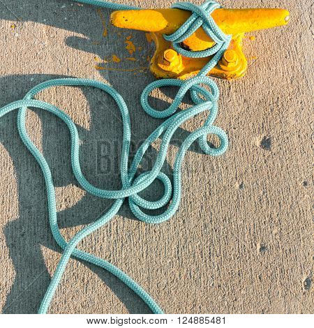 Yellow mooring bollard with blue rope in marina closeup