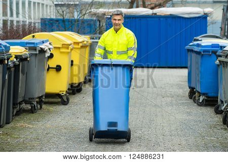 Male Worker Walking With Dustbin On Street