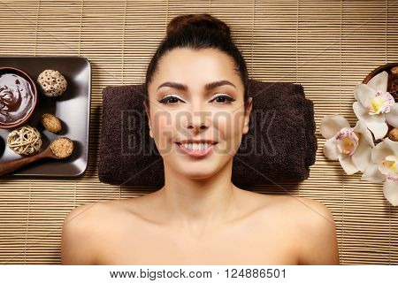 Beautiful young girl lying on massage table in spa salon